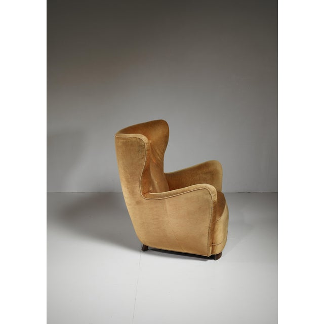 A Danish high, wingback easy chair in the style of Mogens Lassen with legs of stained beech. The chair is upholstered with...