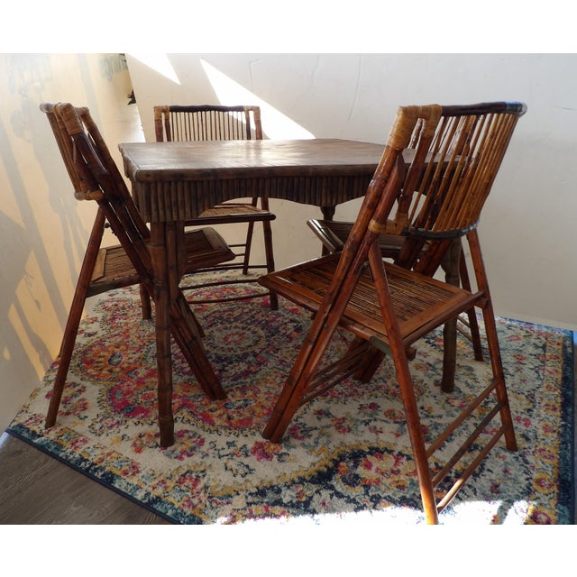 Old Florida rattan and bamboo game table and six chairs. The table and the chairs fold making this not only a unique...
