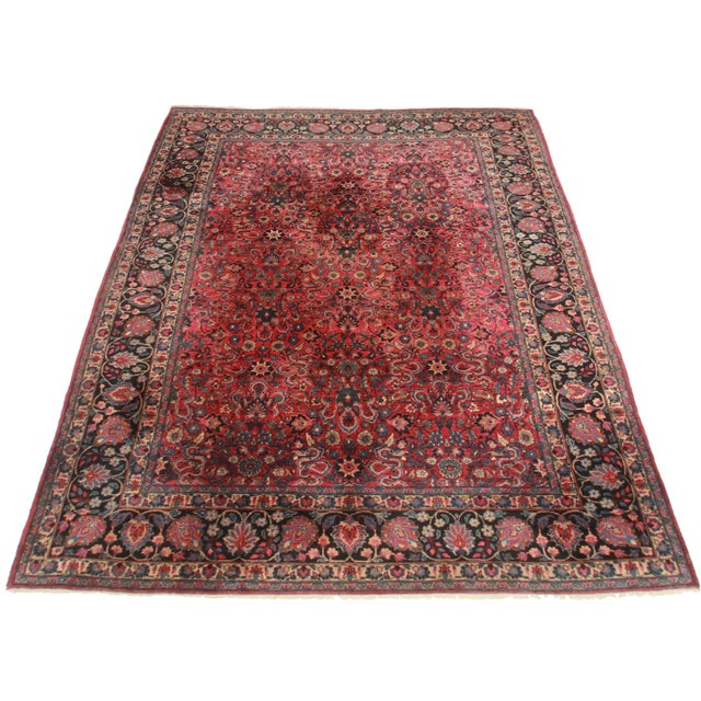 Here is a vintage Persian Mashad rug. Made of hand-knotted wool. Features a rush red background.