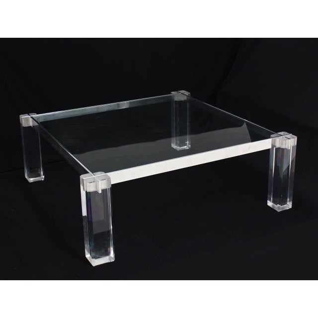 Lucite legs with interlocking stainless steel bars glass top coffee table.
