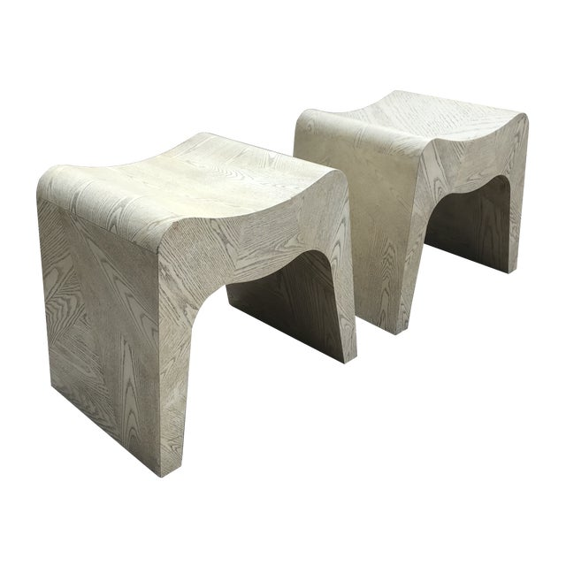 Striking pair of curvilicious vintage waterfall stools. Each is covered in woodgrain bone- to taupe-colored laminate over...