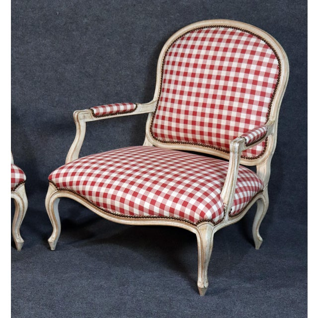 Pair of large red check linen Louis XV style bergere chairs with a factory distressed finish.