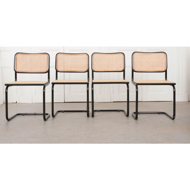 These wonderful Bauhaus-inspired black-lacquered tubular steel side chairs, with natural woven cane seats and backs, are...