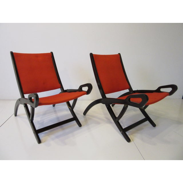 """A pair of rare dark walnut framed """" Ninfea """" folding lounge chairs with the original tight woven red fabric with handle..."""