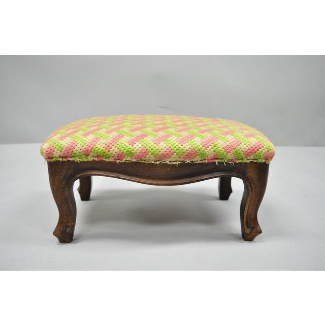 This is a small antique footstool from the early 20th century. The piece is rendered in the French provincial country...