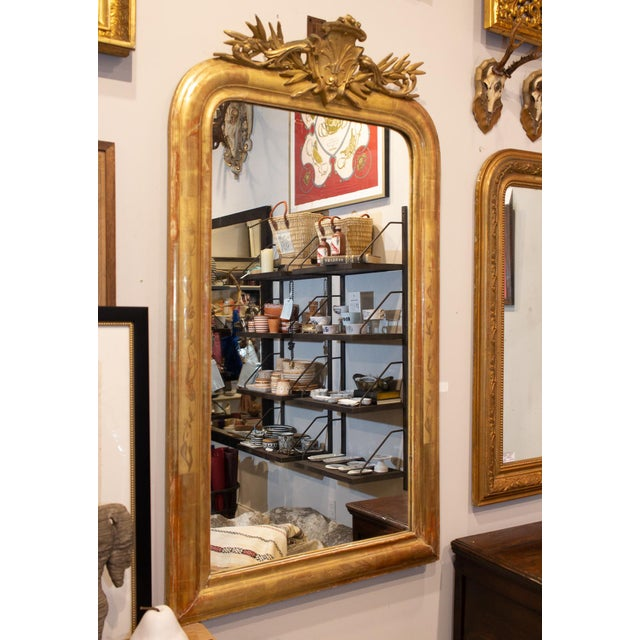 This stunning, bright gold gilt mirror features an ornate cartouche and floral details in the frame. The red tones in the...