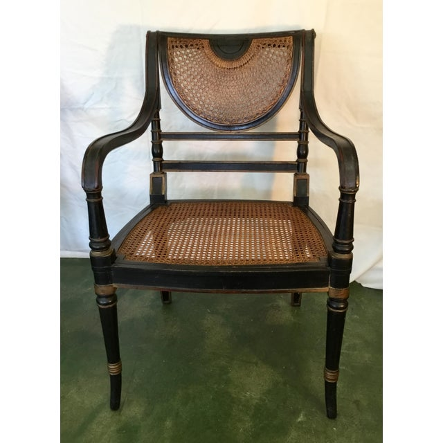 This handsome set of eight French cane chairs are in black with accents of striking gold and red. The back has a half...
