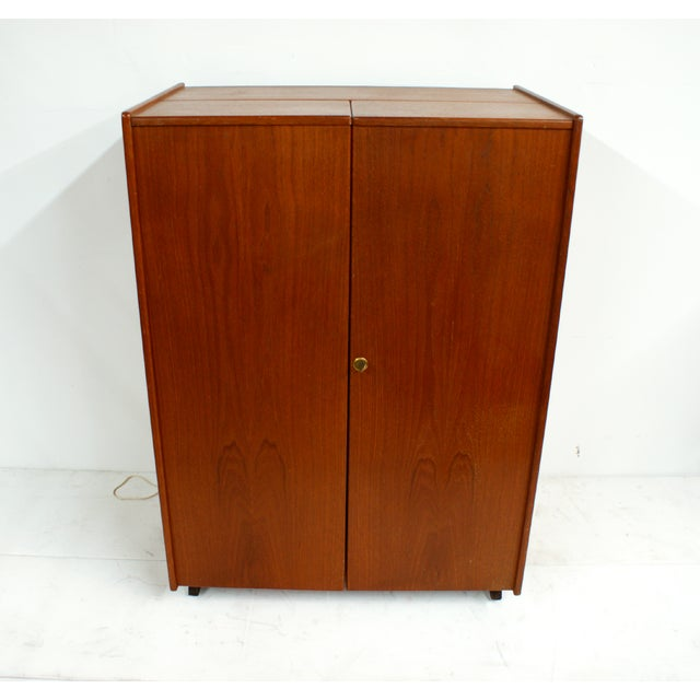1960s Mid Century modern teak fold-out desk cabinet. Beautifully rich in color this lockable storage cabinet includes a...