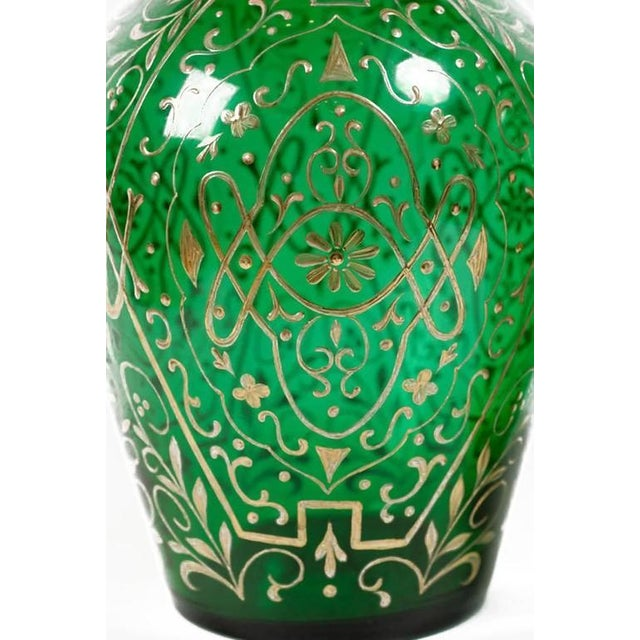 Tall and impressive, these huge green decanters have blown glass bodies with all-over gold-leaf foliate decoration....