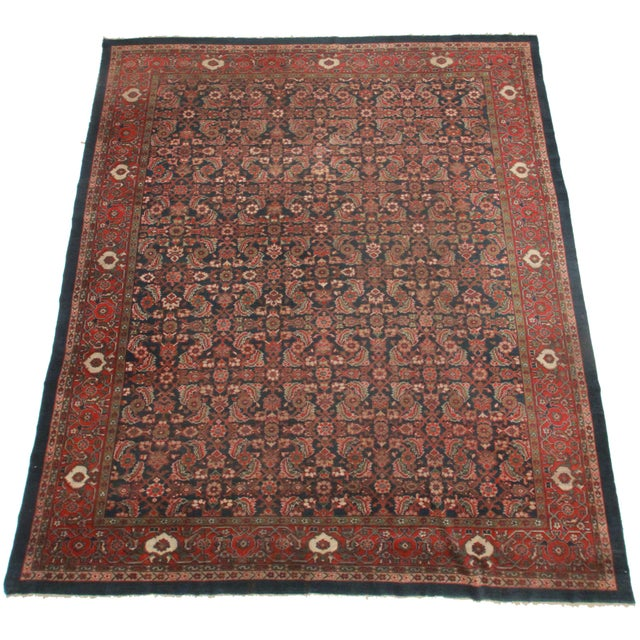 This is an antique Persian Mahal rug. Made of hand-knotted wool. Features a stunning floral design.