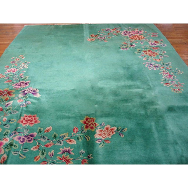 Up for sale is an Antique Chines Rug with a green background and floral designs.