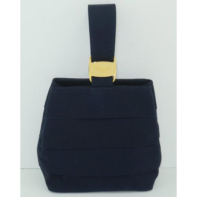 Ferragamo creates a unique diminutive handbag utilizing tiers of dark blue (almost black) grosgrain fabric with a wristlet...