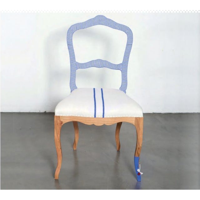 This chair features a white cotton linen upholstered seat with two coordinating blue stripes down the center. The chair...