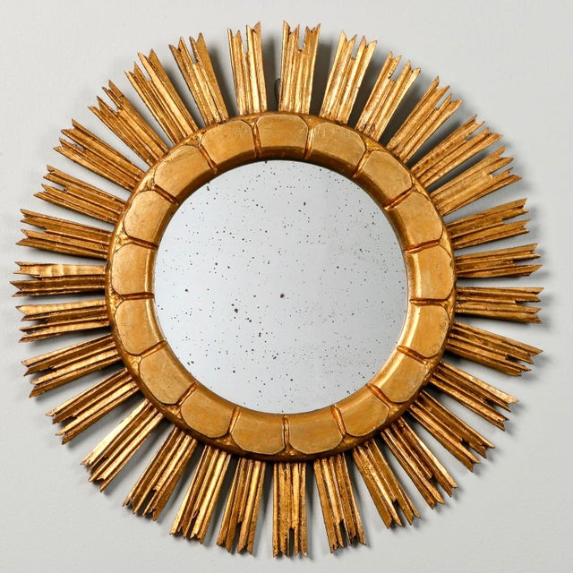 Giltwood mirror in sunburst form has rays with jagged tips and an incised scallop design on the inner frame, circa 1960s....