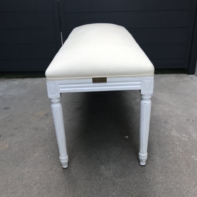 This French inspired bench from Rachel Ashwell features white legs and cream linen upholstery.