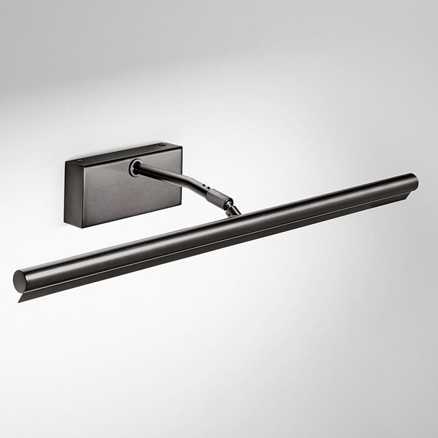 A long black bronze slim picture wall light with a front baffle to prevent glare. The head is adjustable and has an...