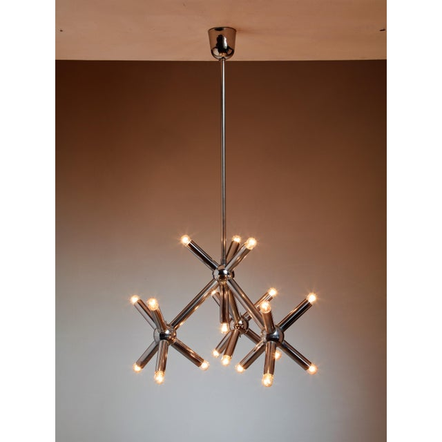 A metal chandelier made of a long stem with 19 smaller arms with light bulbs extending from it.