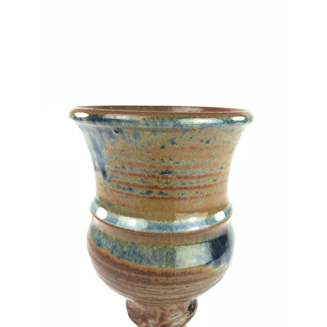 Really cool looking handmade studio pottery stemmed cup with a blue and orange and brown glaze to it.