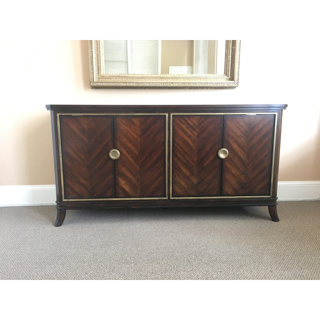 Lovely brown wood sideboard with herringbone pattern on door panels. Funky cool gold trim and knobs. Each cupboard has two...