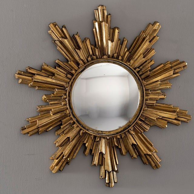 Mid century sunburst mirror has a gilded resin frame and a convex center mirror. Unknown maker.