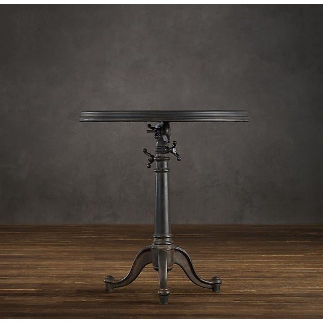 Restoration Hardware heavy French style tilt top table with stepped cast metal rim, cast-iron tripod base with sculptural...