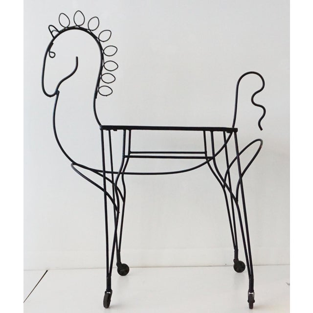 A vintage wrought iron bar cart in the shape of a pony. The piece is on casters with glass top shelf. For use as a bar...