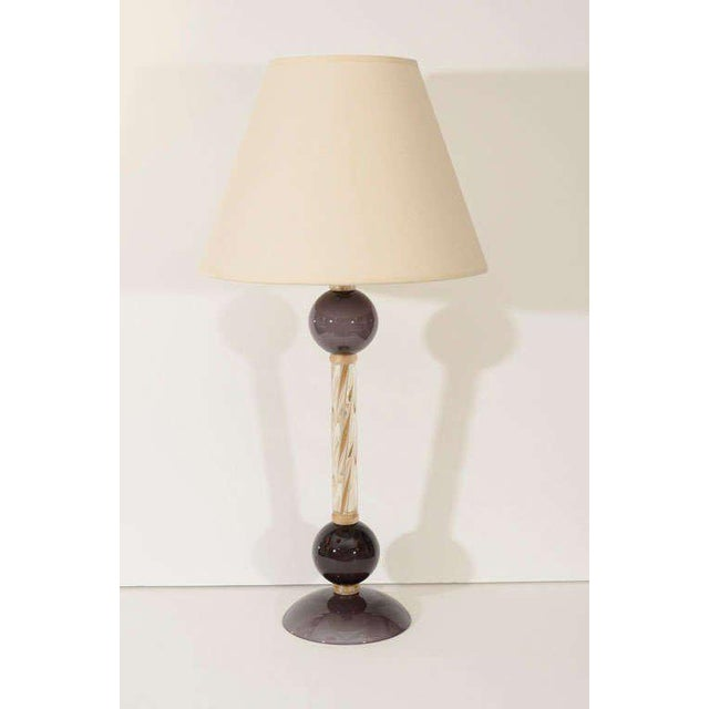An unusual pair of Murano glass lamps composed of a clear glass column with gold leaf inclusions and violet globes at base...