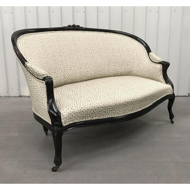 Charming yet sophisticated Victorian settee dressed in professionally upholstered contemporary fabric. Wood frame is...