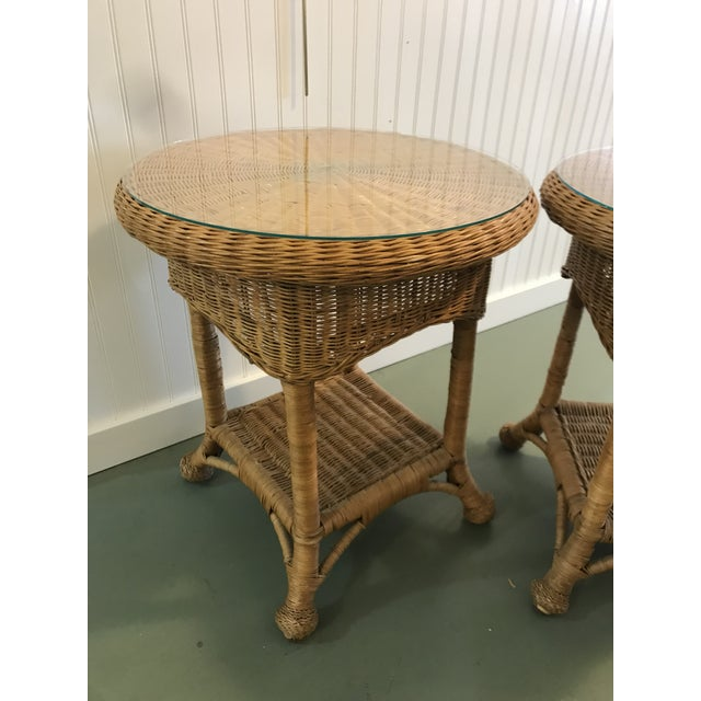 Charming pair of vintage wicker side tables with glass tops. Some discoloration, wear and scratches to the wicker. See pics.