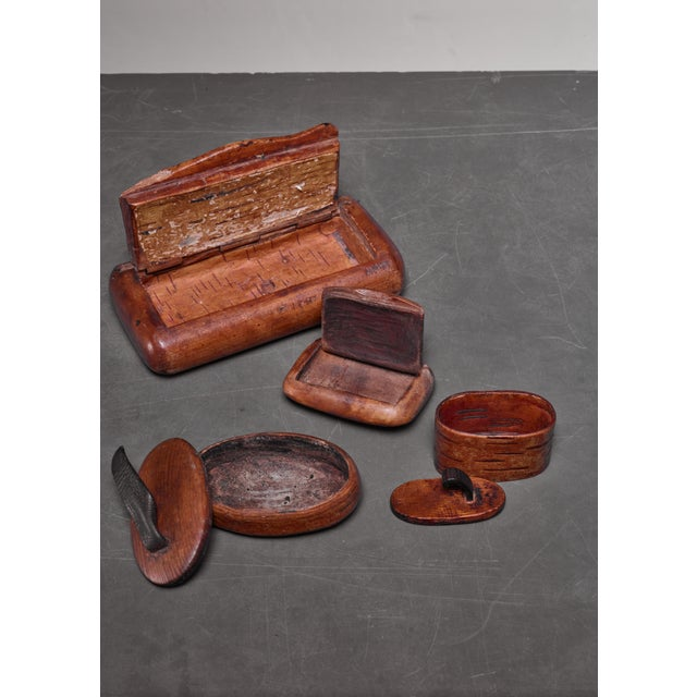 A set of four Swedish folk art boxes made of wood and bark. The boxes have a lid, two of them with a leather grip. These...