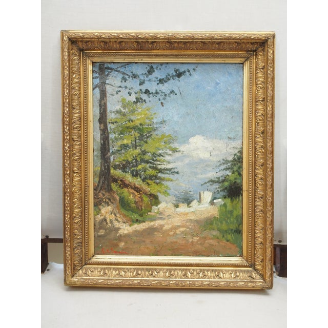 A 19th century oil on canvas landscape painting of a sunlit road winding up a rocky hill. indistinctly signed in the lower...