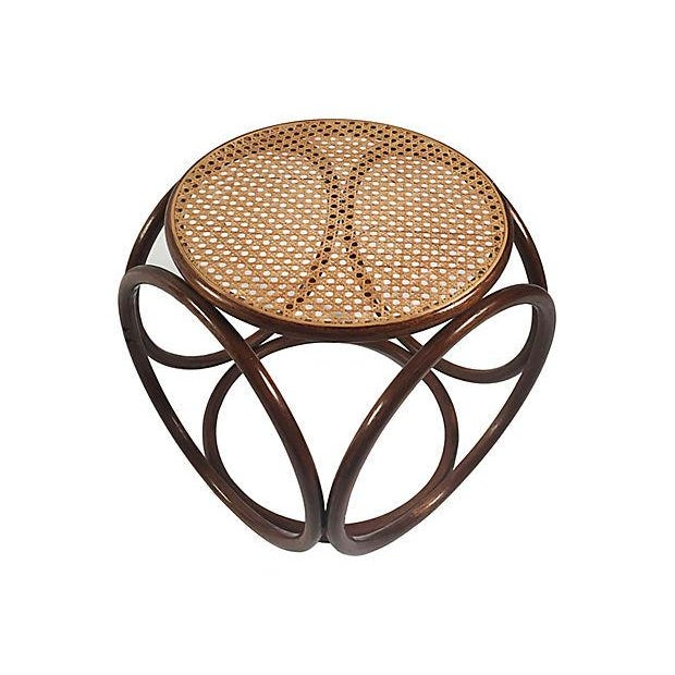 Round rattan footstool with caned top, circa 1960.