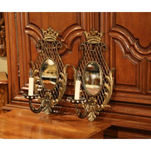 This elegant pair of wall light fixtures were crafted in France, circa 1920. The sconces feature one single light,...