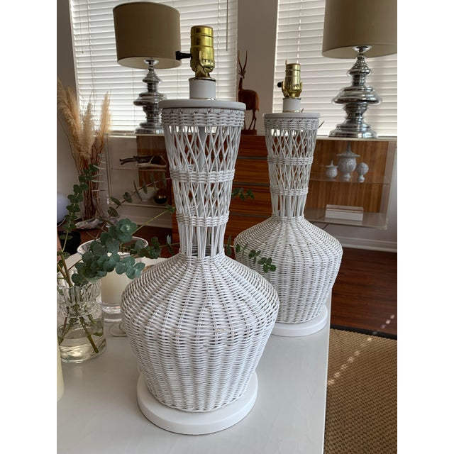 Classic pair of white wicker lamps. Measuring 23H x 10D x 10W, these are in great vintage condition and can be paired with...