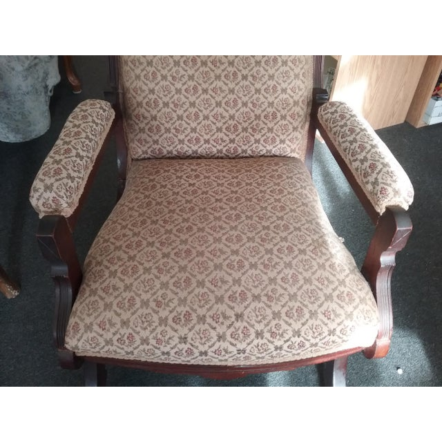 This is an Eastlake style Victorian upholstered platform rocking chair. There are wheels on the base and it has fabric...