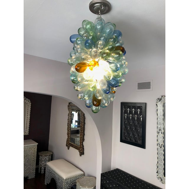 This sculptural light fixture is composed of individual handblown balloon shaped pieces, individually attached to a metal...