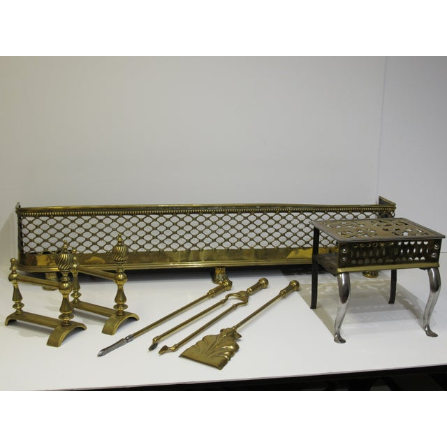 This polished brass fireplace set radiates English elegance with rosette lattice fender on stately lion claw feet, spiral...