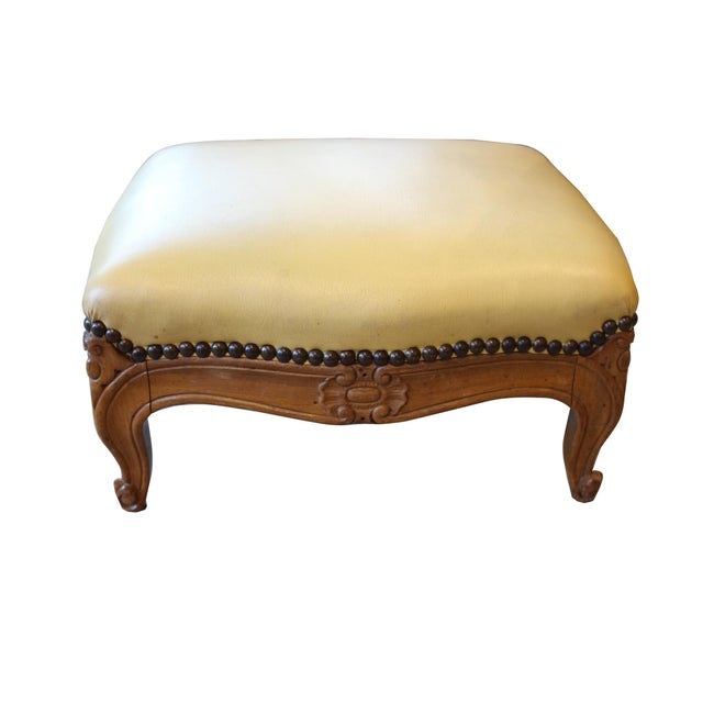 Antique French Louis XV style walnut footstool. Upholstered in yellow leather with brass nailhead detailing.