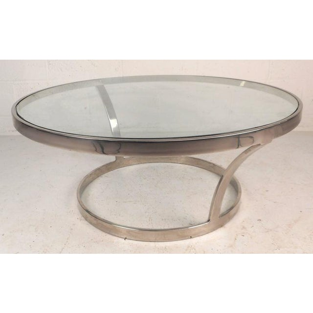 Stunning vintage modern coffee table features a heavy chrome frame with two sculpted side supports underneath a floating...