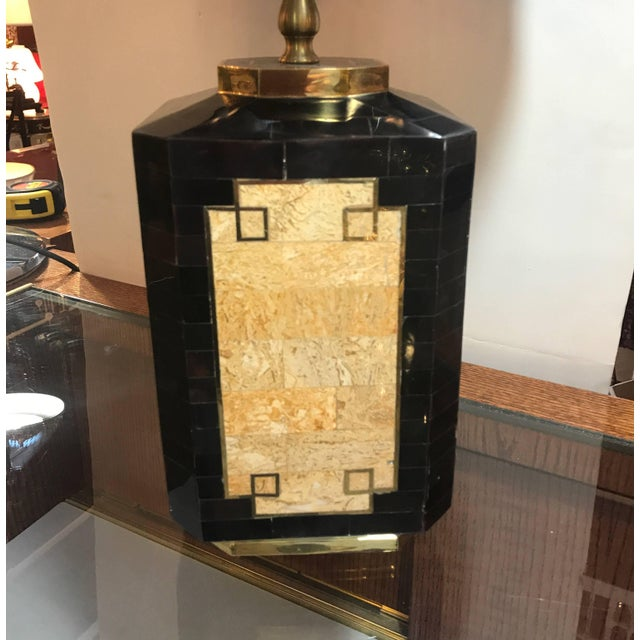 Glamour's pair of stone with brass inlay lamps. The tessellated stone with outlines of brass with a darker stone that is...