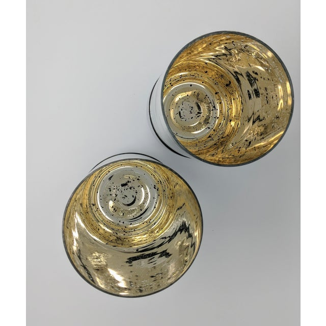 This set of two Mercury Glass Candle Holders are comprised of blown glass that is then treated with a mercury glass...