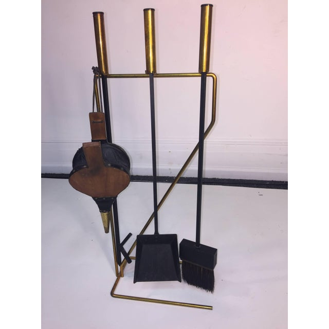 Modernist design brass and black iron fire tools with poker, shovel and brush and teak body bellows with brass end cap....