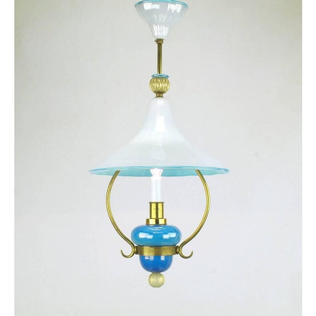 Exceptional handblown Italian Murano cased glass pendant light with brass frame. Blue and white cased glass canopy, hooded...