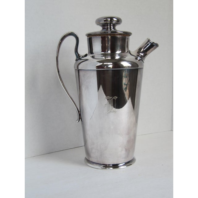 """Art Deco-style silver plate drinks pitcher with cork-lined top and strainer in the spout. Marked on reverse """"Meridien S.P...."""