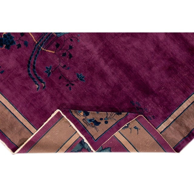 A hand-knotted Chinese Mandarin rug with an artistic design on a purple field brown frame. This rug has accents of blue,...