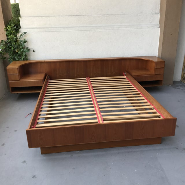 This is an incredible vintage Danish teak queen size floating bed frame by Komfort of authentic Mid-Century quality....