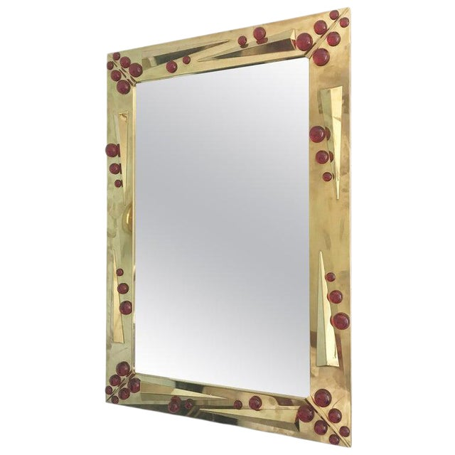 Rectangular mirror in semi-polished brass finish decorated with additional brass inserts and ruby red Murano glass...