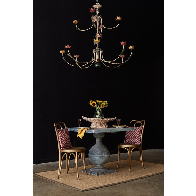 Whimsical French painted iron twelve-light candle chandelier. Features twelve curved arms with yellow and red floral motif...