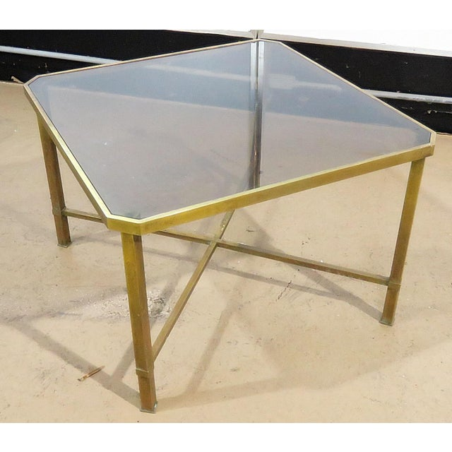 Italian modern coffee table with a smoked glass top on a brass X base.