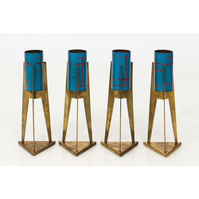 This set of four Italian Modernist brass and enamel votives are finished in a blue and red paint.